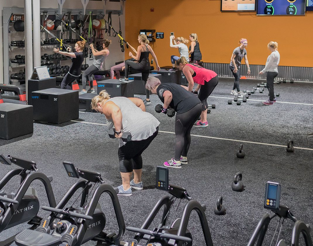 women lifting weights in group fitness class