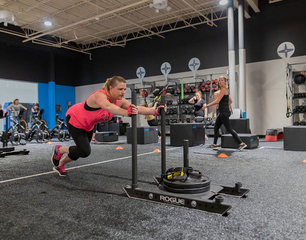 woman pushing weights across fitness training floor
