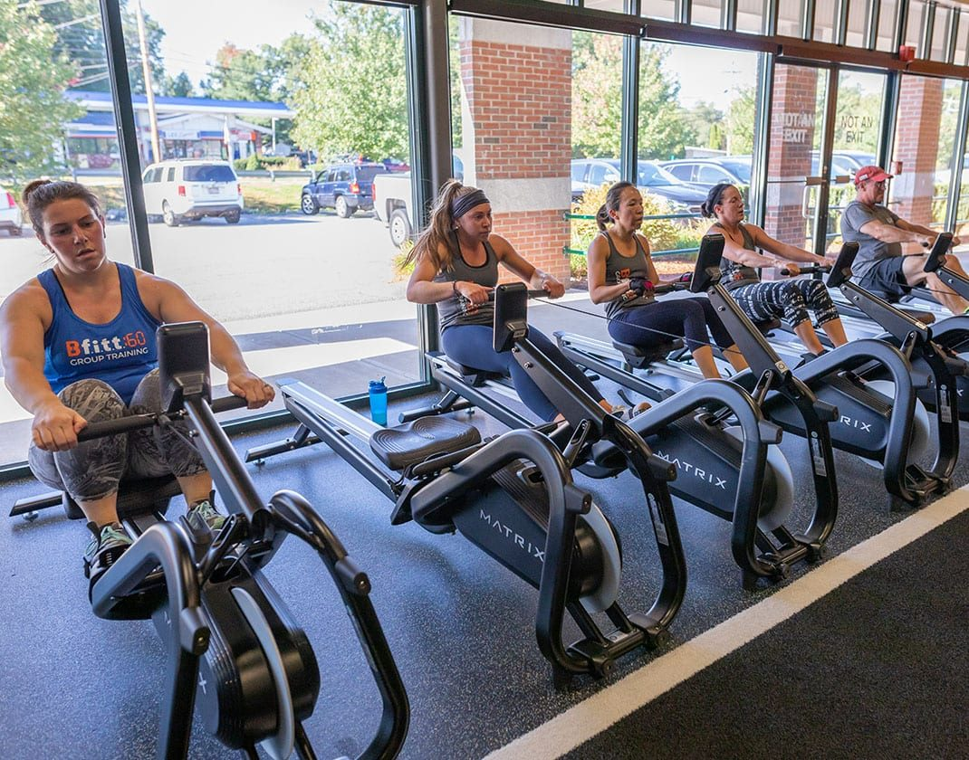 fitness class members on rowing machine