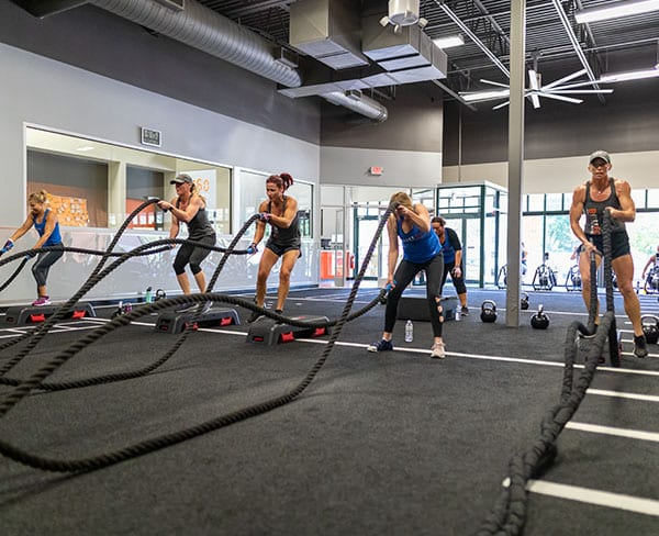 women using combat ropes in fitness class